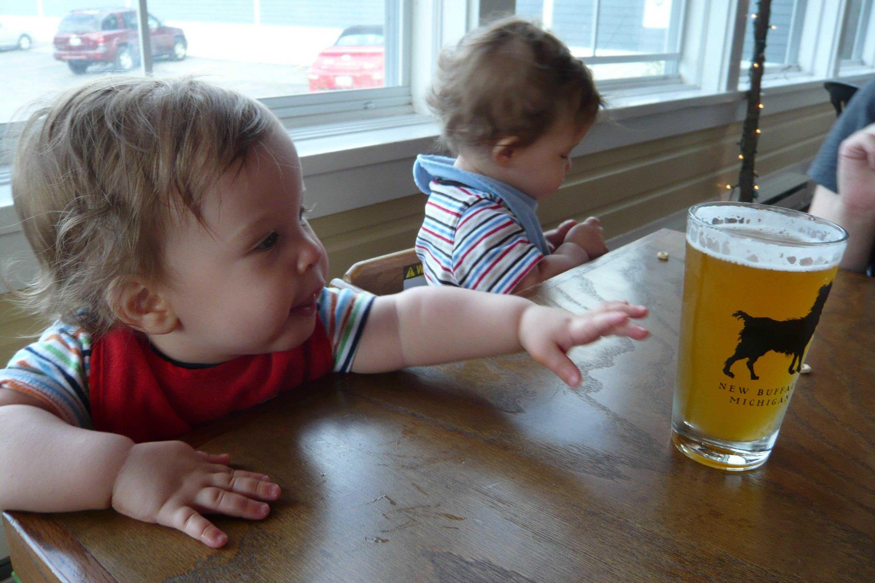 dziecko sięgające po piwo w kuflu