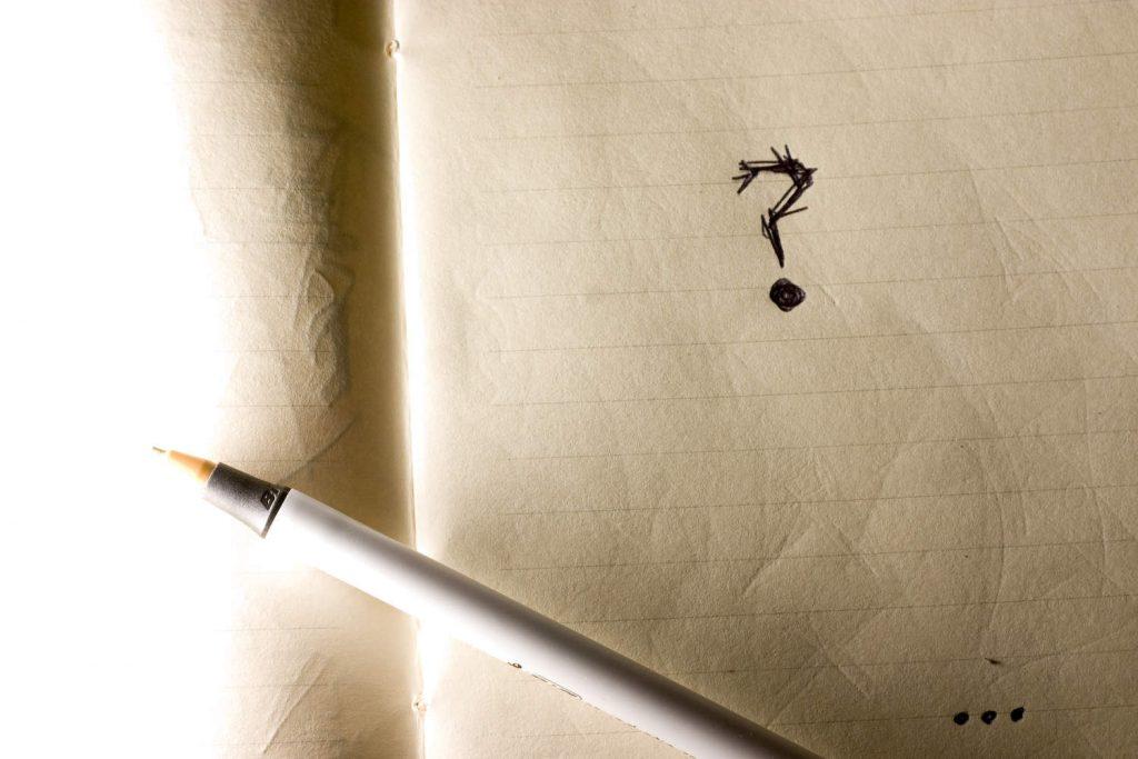 Długopis leży na otwartym zeszycie i obok narysowanego znaku zapytania