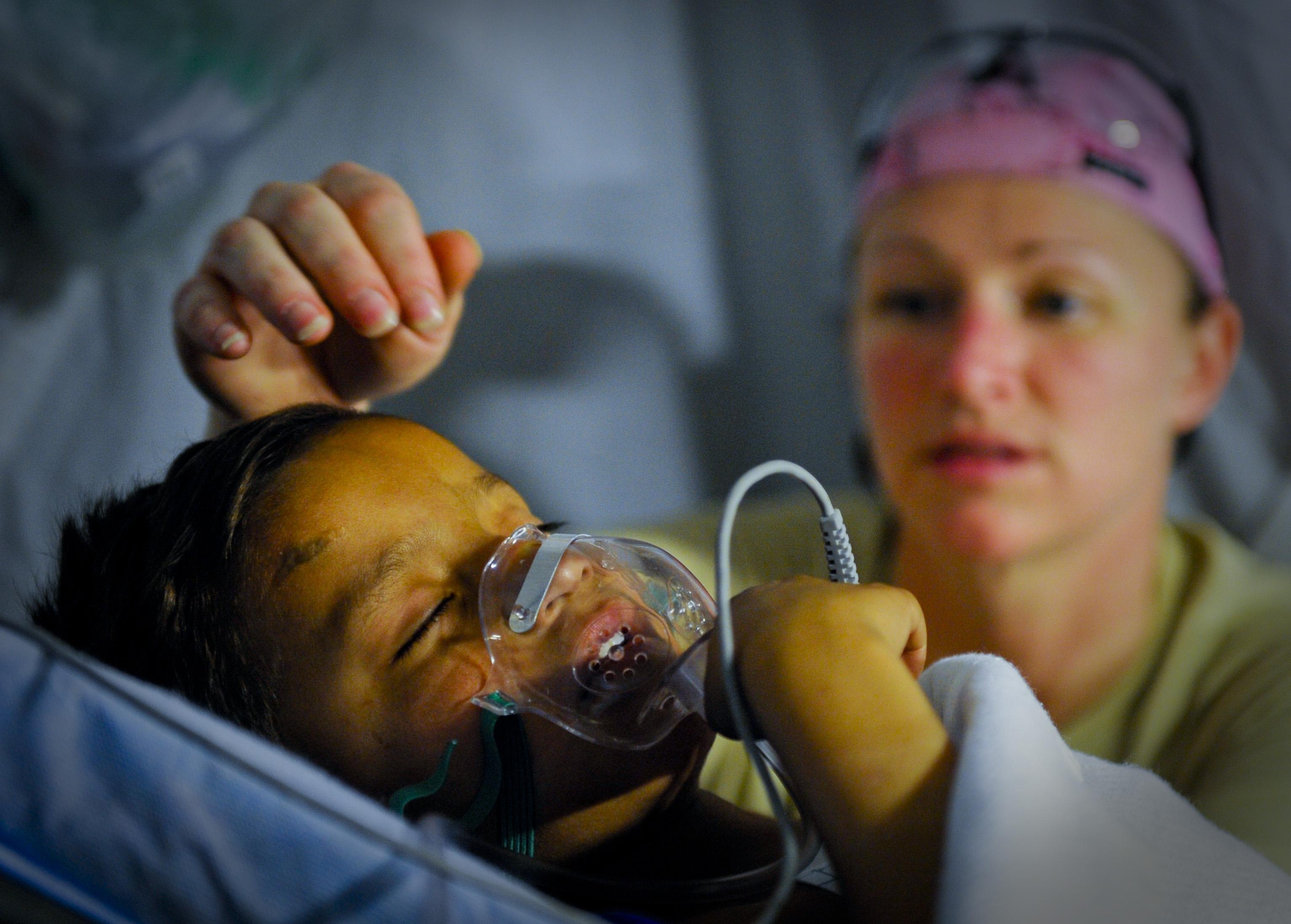 chłopiec z maską tlenową, a w tle lekarka głaskająca chłopca po głowie