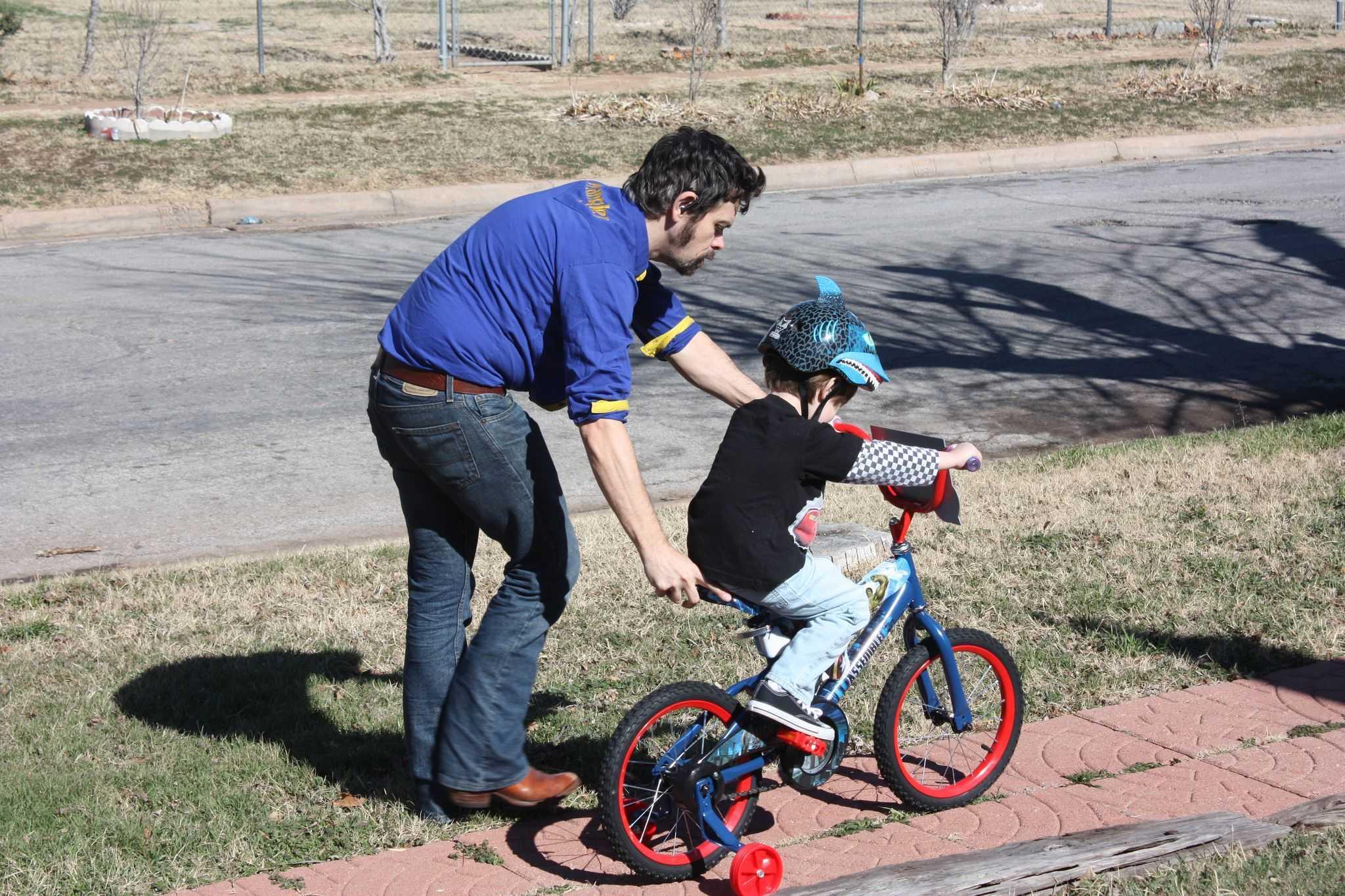 Ojciec pomaga synowi jeździć na rowerze