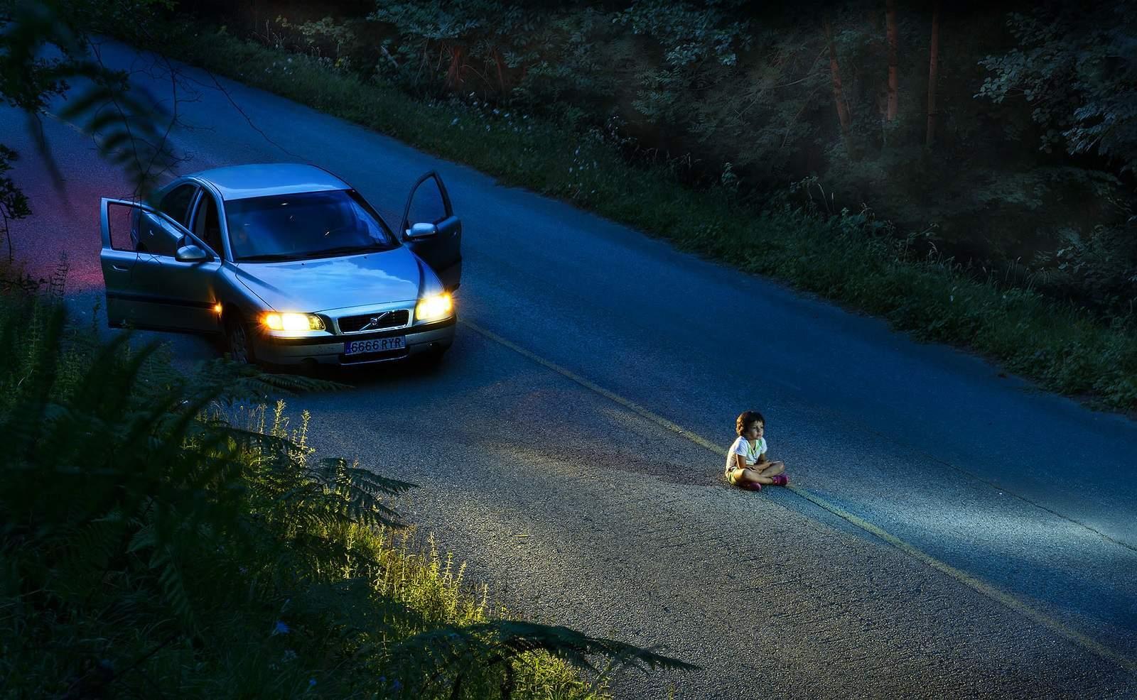 dziecko w światłach reflektorów samochodu