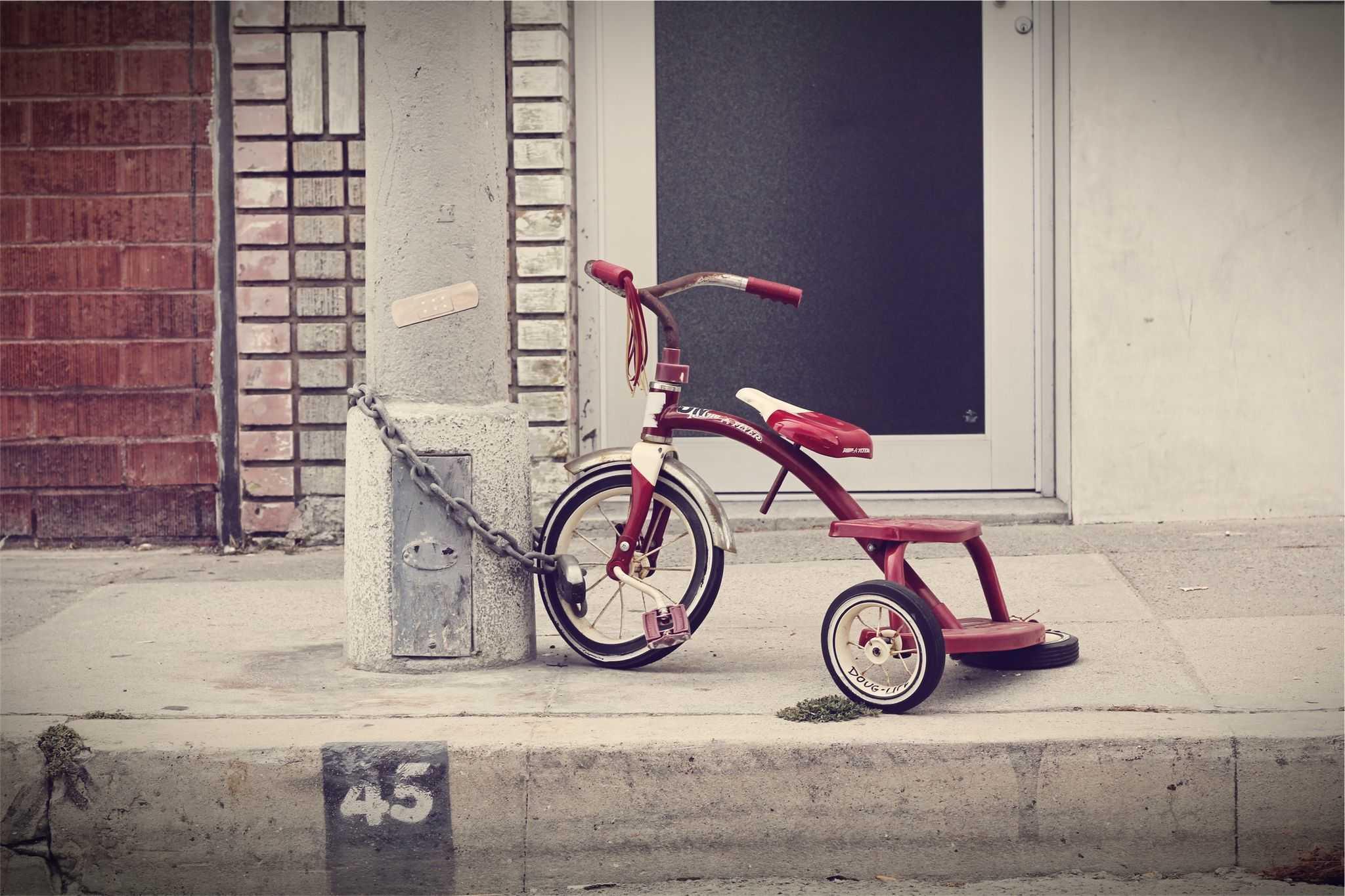 dziecięcy rowerek przywiązany łańcuchem do słupa - gdzie jest dziecko