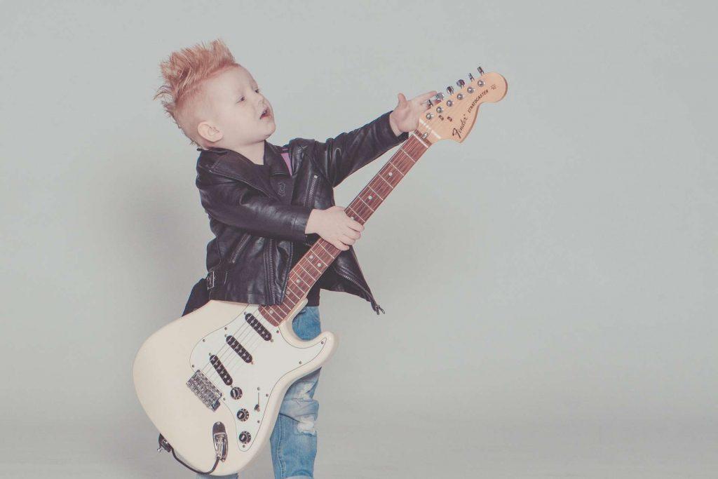 Spersonalizowane piosenki dla dzieci - dziecko próbuje grać na gitarze elektrycznej