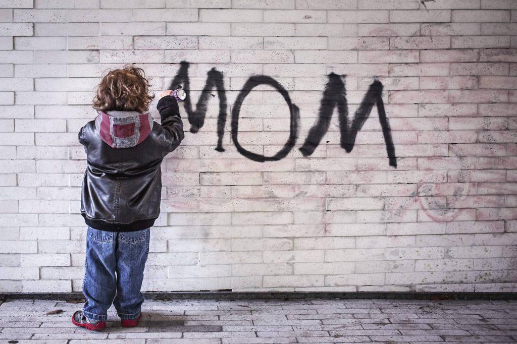 dziecko pisze na murze mom