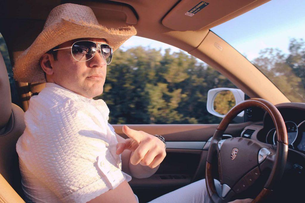 mężczyzna w samochodzie wskazujący palcem w naszą stronę